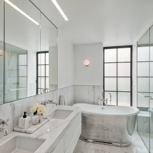 Example of a small trendy master white tile terrazzo floor and white floor bathroom design in New York with white cabinets, white walls, an undermount sink, terrazzo countertops, white countertops, flat-panel cabinets and a hinged shower door