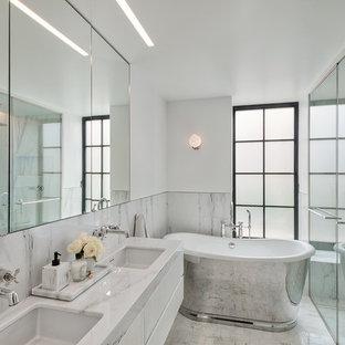 Cette image montre une petite douche en alcôve principale design avec des portes de placard blanches, une baignoire indépendante, un carrelage blanc, un mur blanc, sol en terrazzo, un lavabo encastré, un plan de toilette en terrazzo, un sol blanc, un plan de toilette blanc, un placard à porte plane et une cabine de douche à porte battante.