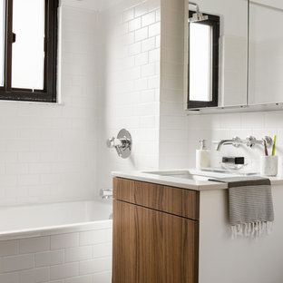 Example of a trendy white tile and subway tile gray floor bathroom design in Charleston with flat-panel cabinets, medium tone wood cabinets, white walls, an undermount sink and white countertops