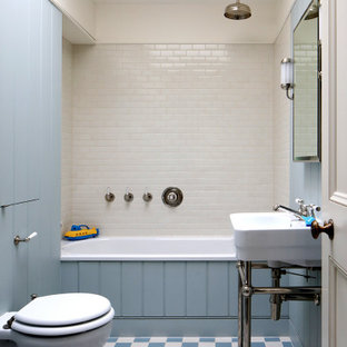Classic family bathroom in London with a built-in bath, a shower/bath combination, white tiles, ceramic tiles and blue walls.