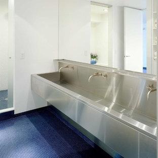 Immagine di una stanza da bagno minimal con ante lisce, pareti bianche, pavimento con piastrelle in ceramica, lavabo integrato, top in acciaio inossidabile e pavimento blu