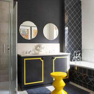 This is an example of a medium sized classic bathroom in London with flat-panel cabinets, a built-in bath, grey floors, black cabinets, black walls and a hinged door.