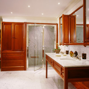 Example of a classic alcove shower design in London with an undermount sink and raised-panel cabinets