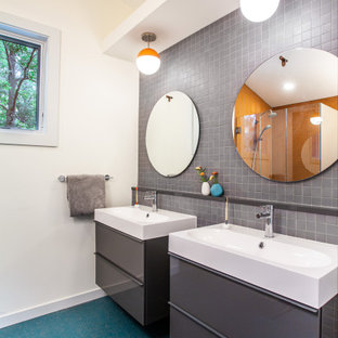 Inspiration for a mid-sized midcentury master bathroom in Detroit with flat-panel cabinets, grey cabinets, a corner shower, a one-piece toilet, gray tile, ceramic tile, white walls, an integrated sink, solid surface benchtops, turquoise floor, a hinged shower door, turquoise benchtops, a double vanity, a floating vanity and vaulted.