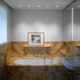 Immagine di una stanza da bagno padronale chic di medie dimensioni con lavabo a consolle, top in marmo, vasca sottopiano, piastrelle arancioni, lastra di pietra, pareti bianche e pavimento in marmo