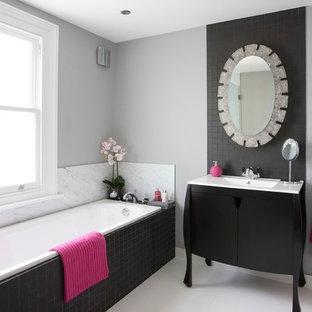 Idee per una stanza da bagno chic con WC sospeso, pareti grigie, pavimento con piastrelle in ceramica, lavabo sottopiano, consolle stile comò, vasca da incasso e piastrelle nere