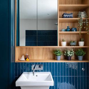 Idéer för ett mellanstort klassiskt blå badrum för barn, med släta luckor, blå skåp, ett platsbyggt badkar, en öppen dusch, en vägghängd toalettstol, blå kakel, keramikplattor, grå väggar, klinkergolv i porslin, ett väggmonterat handfat, träbänkskiva, grått golv och dusch med gångjärnsdörr