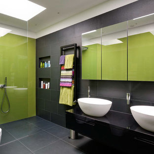 ロンドンの大きいコンテンポラリースタイルのおしゃれなマスターバスルーム (ベッセル式洗面器、黒いキャビネット、オープン型シャワー、オープンシャワー、黒い洗面カウンター、フラットパネル扉のキャビネット、壁掛け式トイレ、グレーのタイル、スレートタイル、緑の壁、スレートの床、人工大理石カウンター、グレーの床) の写真