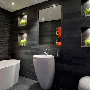 Medium sized contemporary family bathroom in London with a pedestal sink, a freestanding bath, slate tiles, recessed-panel cabinets, dark wood cabinets, a shower/bath combination, a wall mounted toilet, grey tiles, grey walls, slate flooring and grey floors.