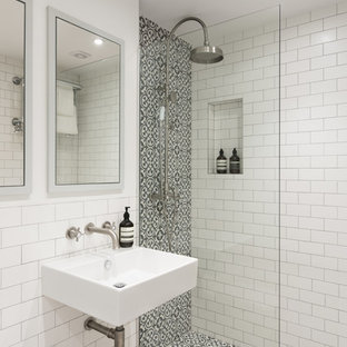 This is an example of a contemporary shower room bathroom in London with a wall mounted toilet, multi-coloured tiles, white tiles, white walls and a wall-mounted sink.