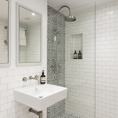 Example of a trendy 3/4 multicolored tile and white tile bathroom design in London with a wall-mount toilet, white walls and a wall-mount sink