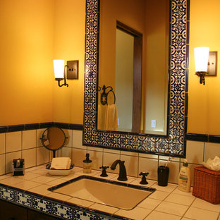 Inspiration for a mid-sized mediterranean 3/4 white tile and ceramic tile bathroom remodel in Sacramento with orange walls, a wall-mount sink, tile countertops, white countertops, raised-panel cabinets and dark wood cabinets