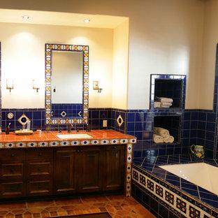 Ispirazione per una grande stanza da bagno padronale mediterranea con vasca sottopiano, piastrelle blu, piastrelle in ceramica, pareti beige, pavimento in terracotta, lavabo sottopiano, pavimento rosso, ante con bugna sagomata, ante in legno bruno, top piastrellato e top arancione