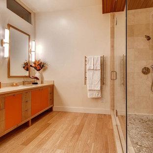 Aménagement d'une salle de bain contemporaine avec un lavabo encastré, un placard à porte plane, des portes de placard oranges, un carrelage beige, un mur beige et un sol en bois clair.