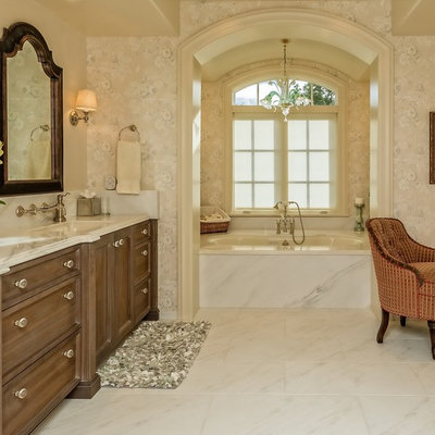 Alcove bathtub - large traditional master porcelain tile and white floor alcove bathtub idea in Denver with recessed-panel cabinets, dark wood cabinets, a one-piece toilet, beige walls, an integrated sink and marble countertops