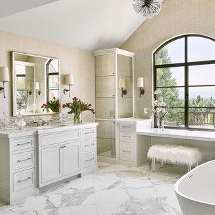 Cette photo montre une grand salle de bain principale chic avec une baignoire indépendante, un sol blanc, un plan de toilette blanc, un placard à porte shaker, des portes de placard grises, un mur beige, un sol en marbre et un lavabo encastré.