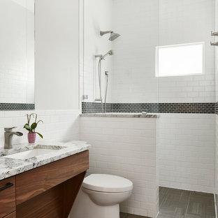 オースティンの中サイズのトランジショナルスタイルのおしゃれな浴室 (白い壁、珪岩の洗面台、グレーの床、フラットパネル扉のキャビネット、中間色木目調キャビネット、段差なし、白いタイル、サブウェイタイル、アンダーカウンター洗面器、オープンシャワー、グレーの洗面カウンター) の写真
