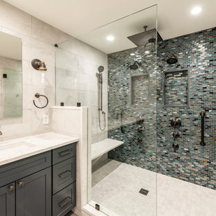 Inspiration for a large transitional master bathroom in Philadelphia with shaker cabinets, blue cabinets, an open shower, a one-piece toilet, white tile, porcelain tile, white walls, wood-look tile, an undermount sink, quartzite benchtops, brown floor, a hinged shower door, white benchtops, a shower seat, a double vanity, a built-in vanity and wallpaper.