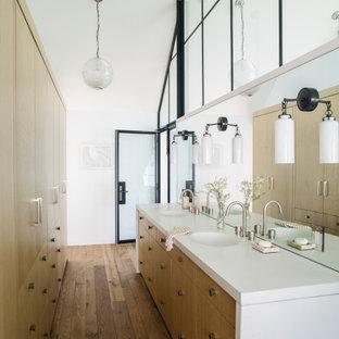 Свежая идея для дизайна: ванная комната в морском стиле с плоскими фасадами, фасадами цвета дерева среднего тона, белыми стенами, паркетным полом среднего тона, монолитной раковиной, коричневым полом, белой столешницей, тумбой под две раковины, встроенной тумбой и сводчатым потолком - отличное фото интерьера