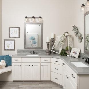 Immagine di una stanza da bagno padronale costiera di medie dimensioni con ante beige, piastrelle grigie, piastrelle di vetro, pareti beige, lavabo sottopiano e top in granito