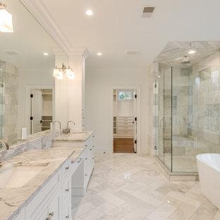 Réalisation d'une douche en alcôve principale tradition avec un placard à porte shaker, des portes de placard blanches, une baignoire indépendante, un carrelage gris, carrelage en métal, un mur blanc, un sol en marbre, un lavabo encastré, un plan de toilette en marbre, un sol gris, une cabine de douche à porte battante et un plan de toilette gris.