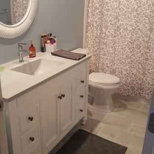 Design ideas for a medium sized traditional family bathroom in Detroit with beaded cabinets, white cabinets, a two-piece toilet, blue walls, porcelain flooring, an integrated sink, marble worktops, grey floors and grey worktops.