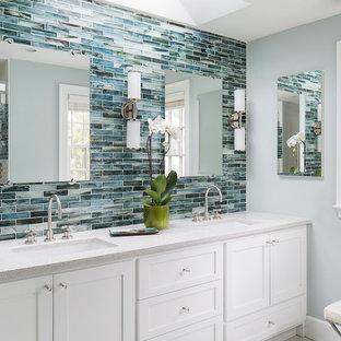 Klassisk inredning av ett en-suite badrum, med ett undermonterad handfat, skåp i shakerstil, vita skåp, bänkskiva i terrazo, en dusch i en alkov, en toalettstol med separat cisternkåpa, vit kakel, porslinskakel, blå väggar och klinkergolv i porslin