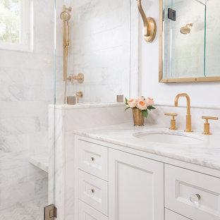 Modelo de cuarto de baño con ducha, actual, pequeño, con armarios estilo shaker, sanitario de pared, baldosas y/o azulejos blancos, baldosas y/o azulejos de piedra, paredes blancas, suelo con mosaicos de baldosas, lavabo bajoencimera, encimera de mármol, puertas de armario blancas, ducha empotrada, ducha con puerta con bisagras y suelo blanco