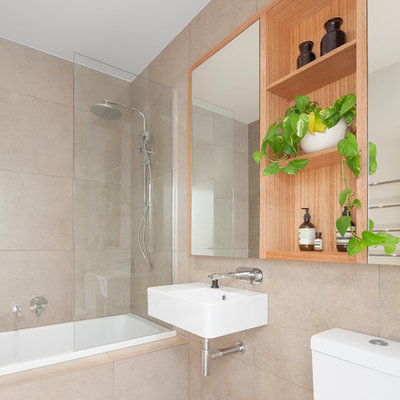 Example of a mid-sized trendy beige tile beige floor bathroom design in Melbourne with a wall-mount sink, a two-piece toilet and beige walls