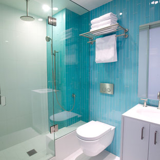 This is an example of a medium sized contemporary shower room in Los Angeles with blue tiles, flat-panel cabinets, white cabinets, an alcove shower, a wall mounted toilet, glass tiles, porcelain flooring, a submerged sink, white floors and a hinged door.