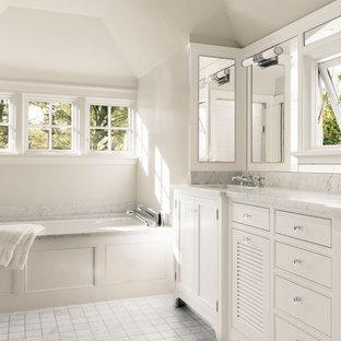 Réalisation d'une salle de bain principale tradition avec un lavabo encastré, des portes de placard blanches, un plan de toilette en marbre, une baignoire encastrée, un carrelage blanc, un carrelage de pierre, un mur blanc, un sol en marbre, un placard avec porte à panneau encastré et un plan de toilette blanc.