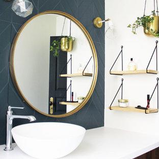 Réalisation d'une salle de bain principale design de taille moyenne avec un combiné douche/baignoire, un lavabo posé, un plan de toilette blanc, un placard à porte affleurante, des portes de placard en bois sombre, une baignoire encastrée, un carrelage bleu, des carreaux de céramique, un mur blanc et un sol en carrelage de céramique.