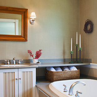 Elegant drop-in bathtub photo in New York with beaded inset cabinets, beige cabinets and beige walls