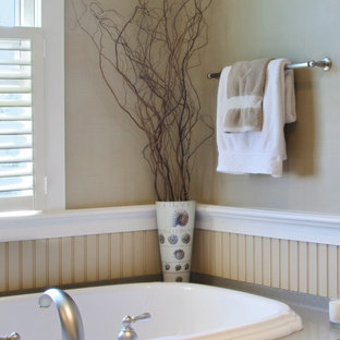 Example of a transitional drop-in bathtub design in New York with beaded inset cabinets, beige cabinets and beige walls