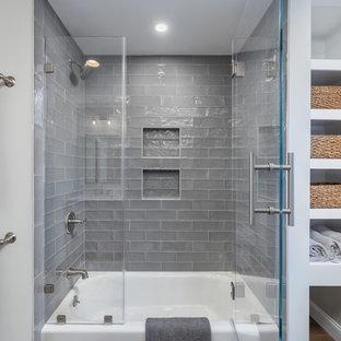 Inredning av ett klassiskt mellanstort flerfärgad flerfärgat badrum för barn, med skåp i shakerstil, grå skåp, ett badkar i en alkov, en dusch i en alkov, en toalettstol med hel cisternkåpa, grå kakel, glaskakel, grå väggar, klinkergolv i porslin, ett undermonterad handfat, bänkskiva i kvarts, flerfärgat golv och dusch med gångjärnsdörr