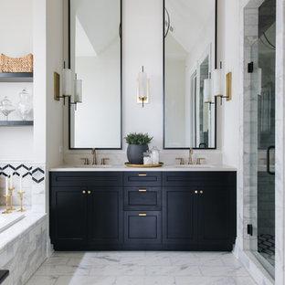Idées déco pour une douche en alcôve campagne avec un placard avec porte à panneau encastré, des portes de placard noires, une baignoire posée, un carrelage blanc, un mur blanc, un lavabo encastré, un sol blanc, une cabine de douche à porte battante et un plan de toilette blanc.
