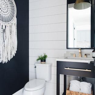 Imagen de cuarto de baño campestre con armarios con paneles lisos, puertas de armario negras, paredes negras, suelo de madera en tonos medios, lavabo bajoencimera, suelo marrón y encimeras blancas