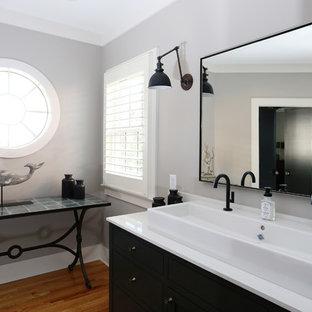 Industriell inredning av ett mellanstort vit vitt en-suite badrum, med luckor med infälld panel, svarta skåp, en dusch i en alkov, svart och vit kakel, tunnelbanekakel, grå väggar, mellanmörkt trägolv, ett fristående handfat, bänkskiva i kvarts, en toalettstol med separat cisternkåpa, orange golv och dusch med gångjärnsdörr