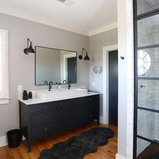 Cette image montre une douche en alcôve principale urbaine de taille moyenne avec un placard avec porte à panneau encastré, des portes de placard noires, un carrelage noir et blanc, un carrelage métro, un mur gris, un sol en bois brun, une vasque, un plan de toilette en quartz modifié, un WC séparé, un sol orange, une cabine de douche à porte battante et un plan de toilette blanc.