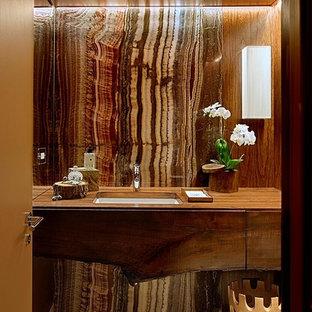 На фото: ванная комната среднего размера в стиле неоклассика (современная классика) с плоскими фасадами, темными деревянными фасадами, коричневыми стенами, врезной раковиной, бежевой плиткой, каменной плиткой, полом из известняка, душевой кабиной, столешницей из дерева и коричневой столешницей