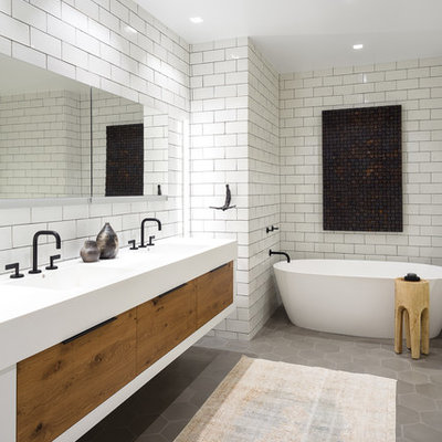 Example of a mid-sized transitional master white tile and subway tile gray floor and cement tile floor bathroom design in Chicago with flat-panel cabinets, medium tone wood cabinets, an integrated sink, white countertops and white walls