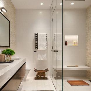 Создайте стильный интерьер: большая главная ванная комната в современном стиле с плоскими фасадами, столешницей из искусственного камня, душем без бортиков, бежевой плиткой, удлиненной плиткой, полом из керамогранита, врезной раковиной, белым полом, душем с распашными дверями, темными деревянными фасадами и белой столешницей - последний тренд