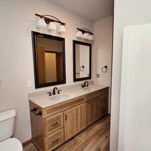 Design ideas for a medium sized country family bathroom in Other with recessed-panel cabinets, medium wood cabinets, an alcove bath, a shower/bath combination, a two-piece toilet, white walls, medium hardwood flooring, an integrated sink, laminate worktops, brown floors, a shower curtain and beige worktops.