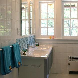 Esempio di una piccola stanza da bagno minimalista con lavabo integrato, ante grigie, vasca/doccia, pavimento alla veneziana, top in superficie solida, piastrelle blu, piastrelle di vetro e pareti bianche