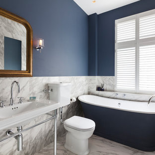 Design ideas for a medium sized traditional ensuite bathroom in London with a freestanding bath, a two-piece toilet, white tiles, blue walls, marble flooring, a console sink, white floors and marble tiles.