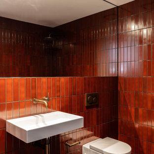 Foto på ett funkis badrum, med en vägghängd toalettstol, röd kakel, ett väggmonterat handfat och grått golv