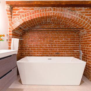 Bild på ett funkis en-suite badrum, med ett avlångt handfat, släta luckor, ett fristående badkar och orange väggar