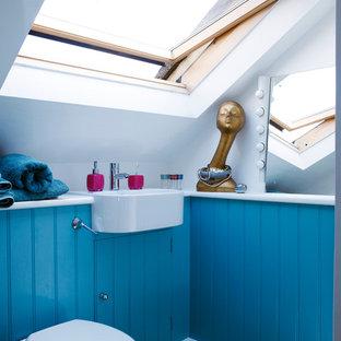 Imagen de cuarto de baño contemporáneo, pequeño, con lavabo suspendido, puertas de armario azules, sanitario de pared, paredes blancas y suelo de madera en tonos medios