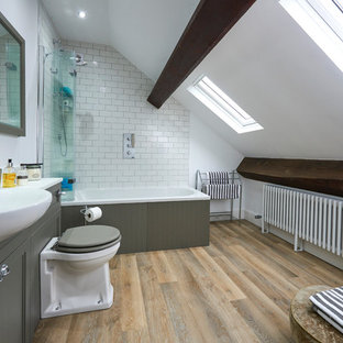 Traditional ensuite bathroom in Other with recessed-panel cabinets, grey cabinets, a built-in bath, a shower/bath combination, metro tiles, white walls, medium hardwood flooring, a built-in sink, brown floors, an open shower and white worktops.