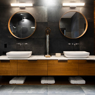 Неиссякаемый источник вдохновения для домашнего уюта: большая главная ванная комната в современном стиле с плоскими фасадами, черной плиткой, керамогранитной плиткой, черными стенами, полом из керамогранита, настольной раковиной, мраморной столешницей, серым полом, белой столешницей и фасадами цвета дерева среднего тона